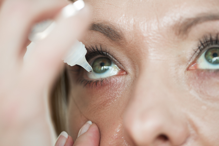 A woman is putting eye drops in her eye.